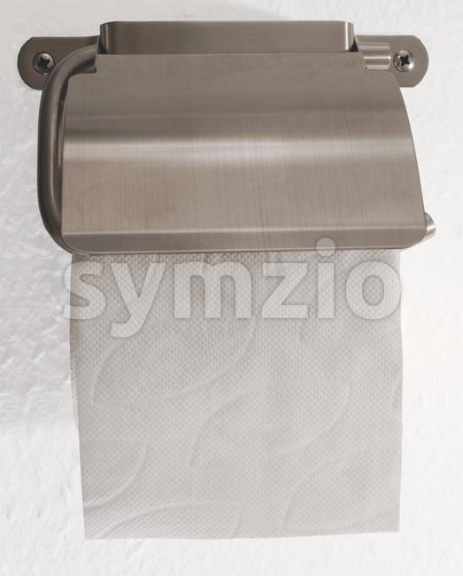 Toilet roll holder with sheet of toilet paper visible on white ingrain wallpaper