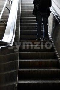 Man moving up with escalator Stock Photo