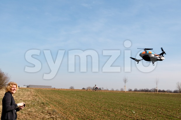 STUTTGART - MARCH 18: Young adults playing with the AR DRONE Quadricopter of manufacturer Parrot SA (www.parrot.com) at a field ...