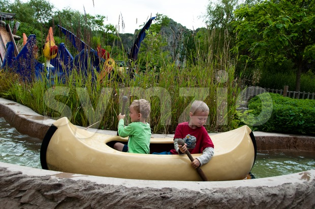Two boys paddling in their canoe at Legoland Stock Photo