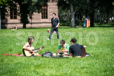 Students playing guitar and having fun in the park Stock Photo