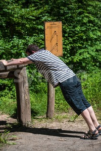 Casual middle aged man doing gymnastic exercises in the forest Stock Photo