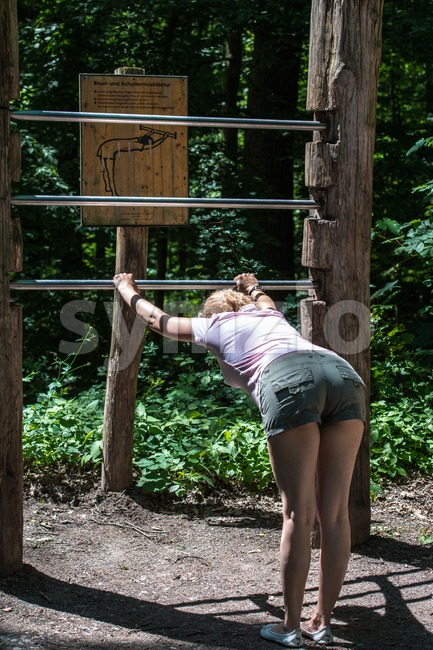 STUTTGART, GERMANY - June 16, 2013: A casual middle aged woman is doing gymnastic exercises at the get-fit-trail in the ...