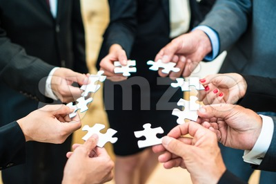 Teamwork - Business people solving a puzzle Stock Photo