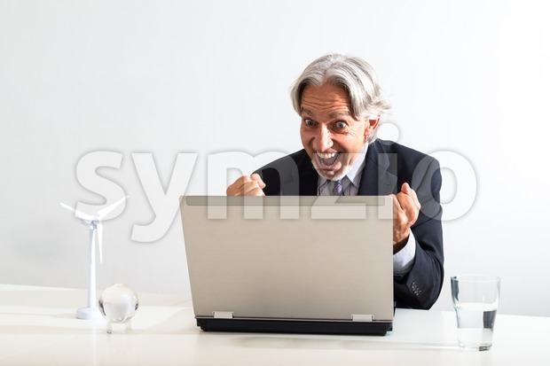 Successful businessman cheering behind his laptop in a modern bright office. The white desk is decorated with the model of ...