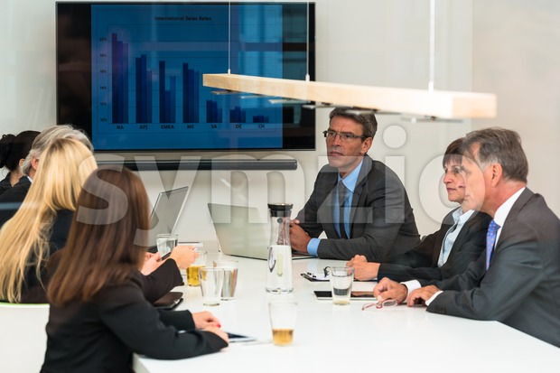 Mixed group in business meeting seen through glass door Stock Photo