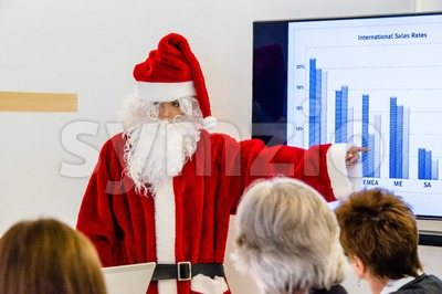 Female Santa Claus presenting in business meeting Stock Photo