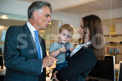 Businesswoman with small child in the office, discussing with her boss Stock Photo