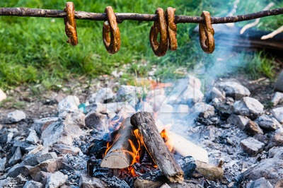 Gernan brezels on a stick over a fire Stock Photo