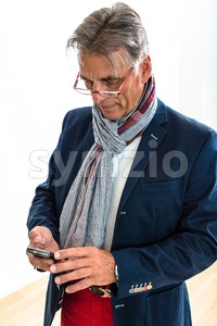 Stylish pensioner checking his mobile phone Stock Photo