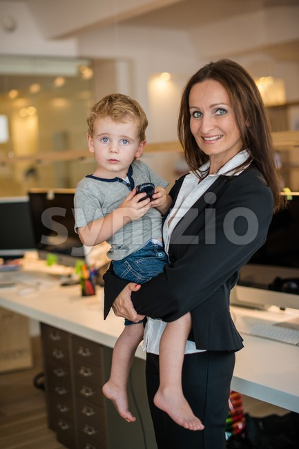 Reconciliation of family and work life: Attractive brunette woman in business attire proudly carrying a small barefoot boy in her ...
