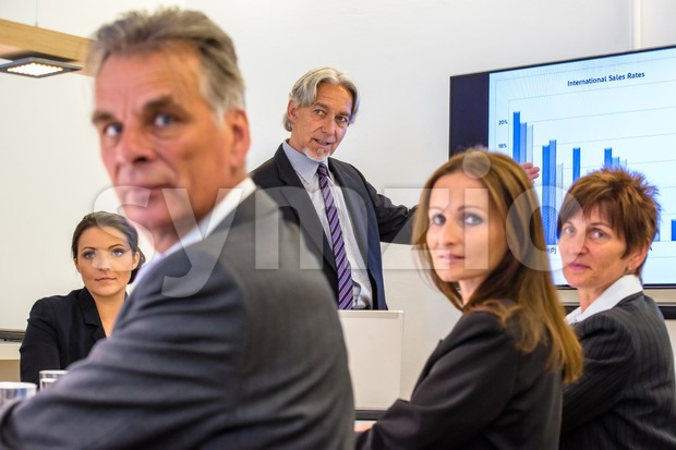 Mixed group in business meeting with laptops and projection screen, looking towards the camera whilst discussing the latest sales figures