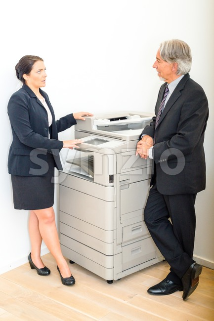 Colleagues talking at  copying machine in the office Stock Photo