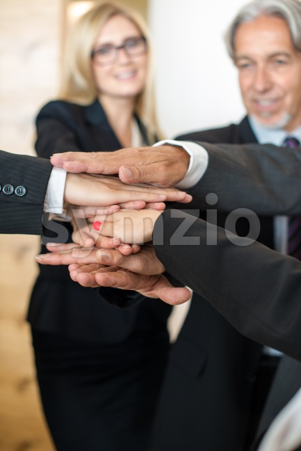 Multiracial group of seven diverse businesspeople standing in a circle joining hands in a team with office scenario in the ...