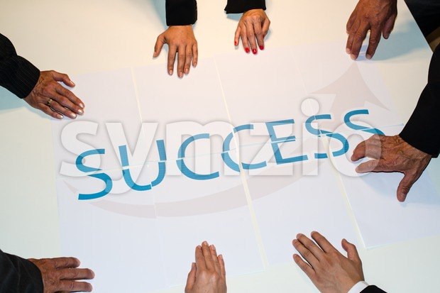 Teamwork means Success : Group of business people assembling the word success spread over several papers - represent team support ...