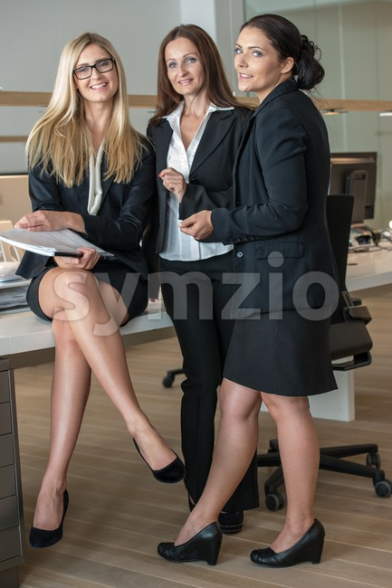Three Businesswomen In Office Working On A Document Stock Photo