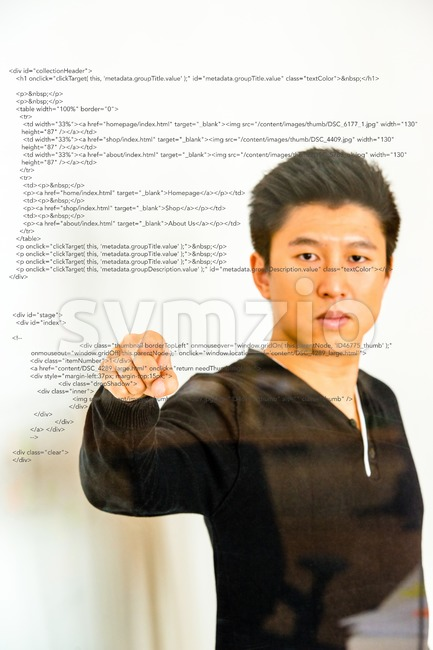 Asian guy pointing towards a potential error in sourcecode projected on glass with reflections. Concept for innovative forms of workspaces ...