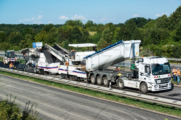 Tipper unloading fresh asphalt from body into tracked paver during pavements construction works Stock Photo