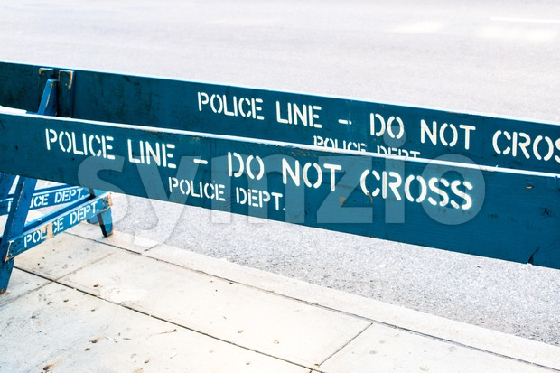 Wooden blue Police barrier saying POLICE LINE - DO NOT CROSS, POLICE DEPT.