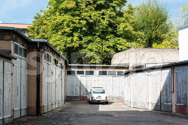 STUTTGART, GERMANY - OCTOBER 3, 2013: A classic Mini Cooper car is parked in front of garages in a backyard ...