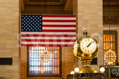 Old Clock and US flag at Grand Central Terminal Stock Photo