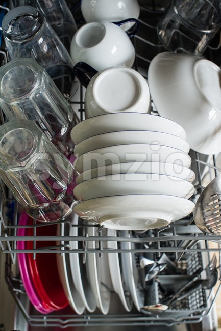 Dishwasher after cleaning process with plates, cups, glasses, cutlery and plastic boxes