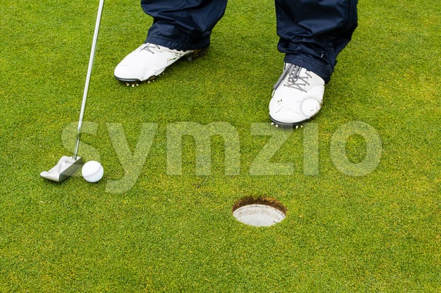 Golf player hitting the ball close-up on whole