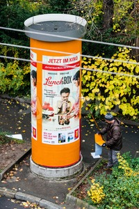 Advertising column being updated with new promotion Stock Photo