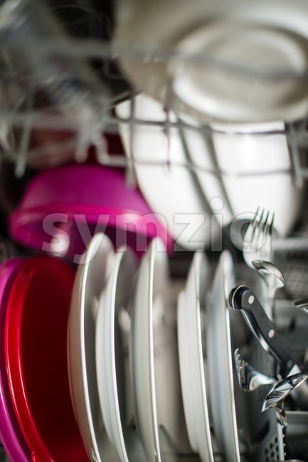 Dishwasher after cleaning process with plates, cups, glasses, cutlery and plastic boxes - shallow depth of field