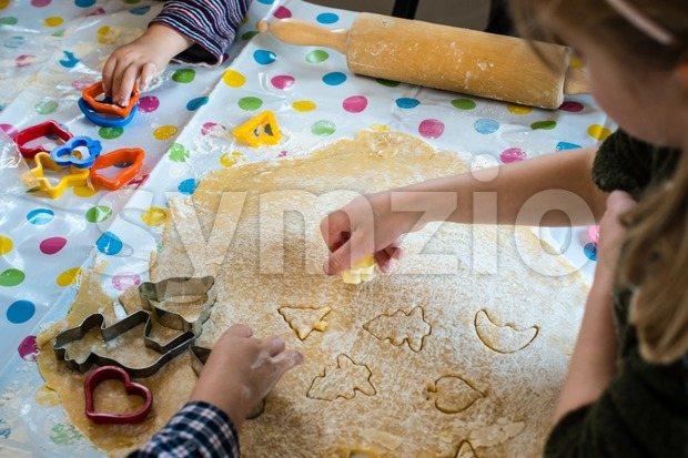 Children Baking Christmas Cookies cutting pastry with a cookie cutter Stock Photo