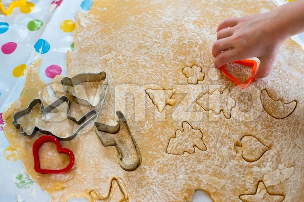 Children baking Christmas cookies: Cutting pastry with a cookie cutter on a colorful table cloth