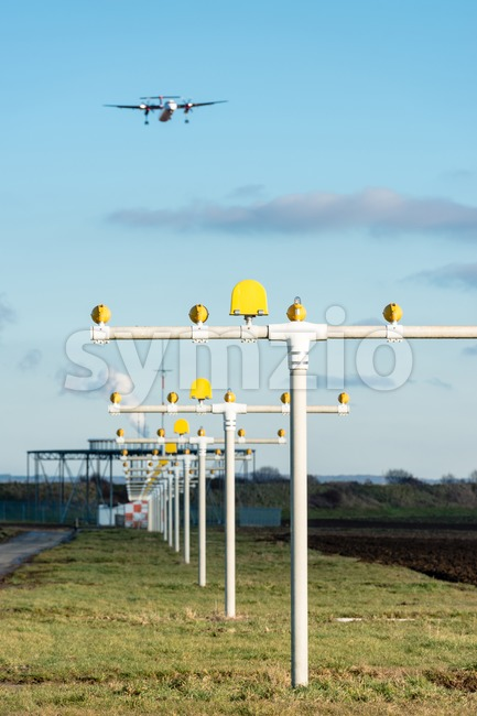 Airport landing lights with airplane approaching runway lighting and radar