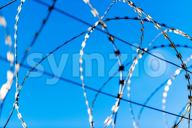 Fence with barbed wire in front of great blue sky - concept for freedom, liberty or prison
