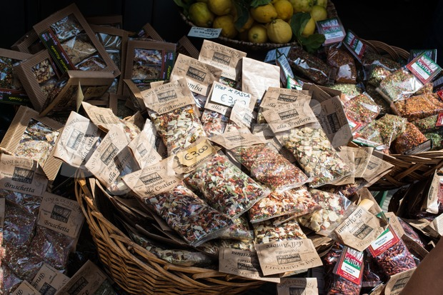 MANAROLA, ITALY - MAY 22, 2013: Selection of dried herbs, spices and fresh lemons for sale in front of a ...