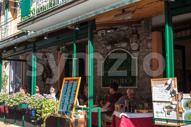 MANAROLA, ITALY - MAY 22, 2013: Tourists enjoying their holidays in the sun outside the cozy trattoria (tavern) La Scogliera ...