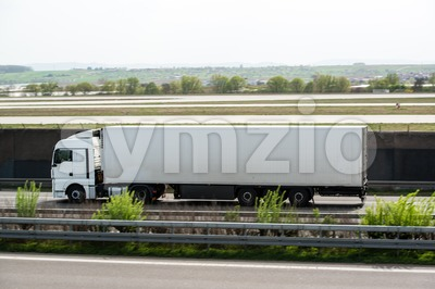 White truck moving on a highway Stock Photo