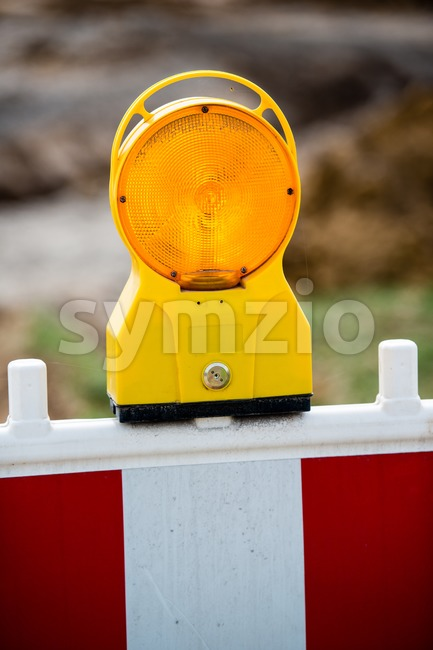 Yellow signal lamp warning against a building site with red and white barrier