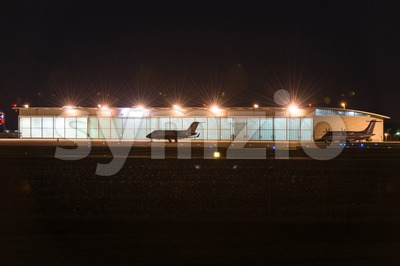 Private jets parked in front of hangar at nigt Stock Photo