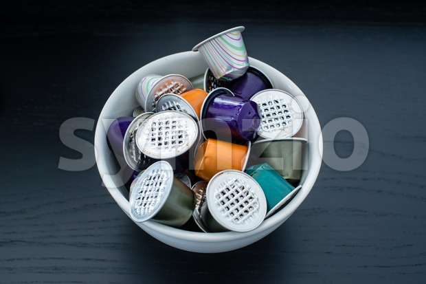 Colourful used gourmet coffe capsules in a bowl on dark wooden table