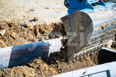 Closeup of dump truck being filled by excavator Stock Photo