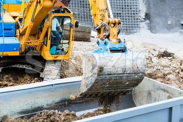 Closeup of excavator filling a dump truck Stock Photo
