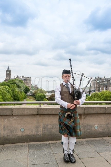Scottish Bagpiper in Edinburgh with the city in the background Stock Photo