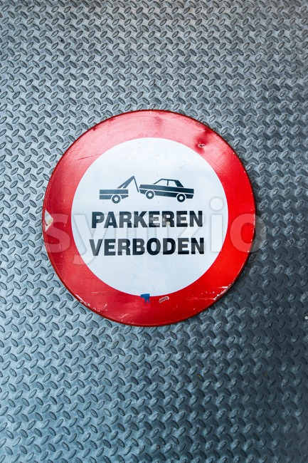 "Dutch no parking sign with wording ""parkeren verboden"" and a car being towed away on metal door background"