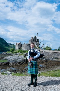 Bagpipe player in front of famous Eilean Donan Castle in the highlands of Scotland with great blue sky background Stock Photo