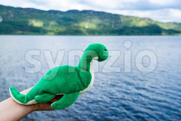 Nessie the mysterious and cute monster as a cuddly toy is held by a female hand over Loch Ness