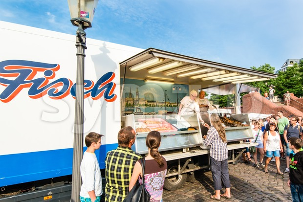 HAMBURG, GERMANY - JULY 20, 2014: A fishmonger and his assistant are selling fish on the traditional Hamburg Fish Market ...