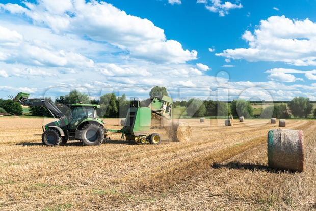Tractor throwing out hay roll during harvest on a field in late summer