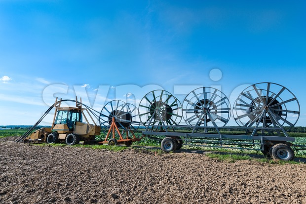 A tractor with trailers is laying fiber optic cables - glass fibers are employed as fiber optic cable for data ...