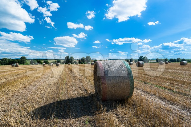Hay bales on the field after harvest with great blue autumn sky