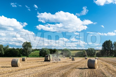 tractor generating hay rolls Stock Photo